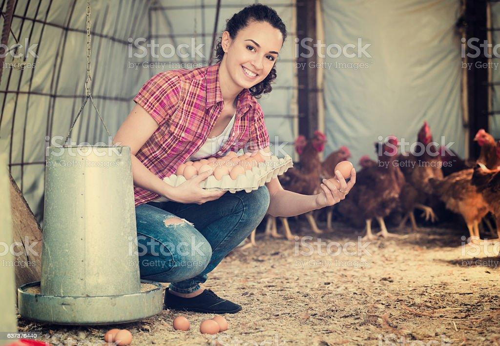 Cheerful female farmer carrying eggs - Photo