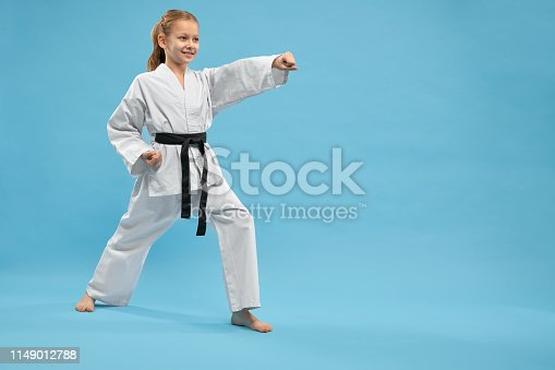 View from side of cheerful female fighter standing in stance and punching with hand in studio. Smiling girl wearing kimono practising karate and jujitsu on blue isolated background. Concept of sport.