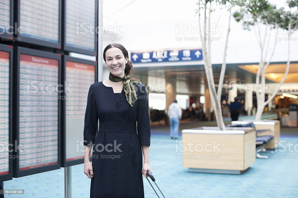 Cheerful Female Flight Attendant By Airport Departure Board stock photo