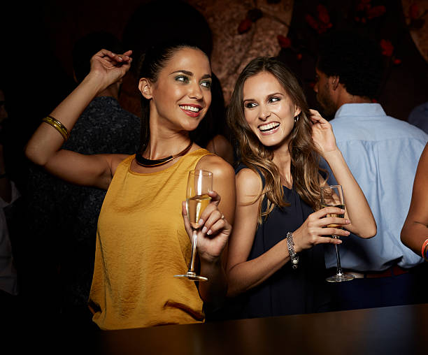 Cheerful female friends dancing in nightclub stock photo
