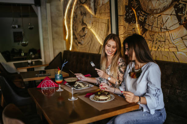 Cheerful female friends eating at restaurant stock photo