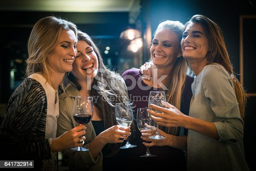 A photo of cheerful friends having drinks. Happy young women are in casuals. They are enjoying social gathering at bar.