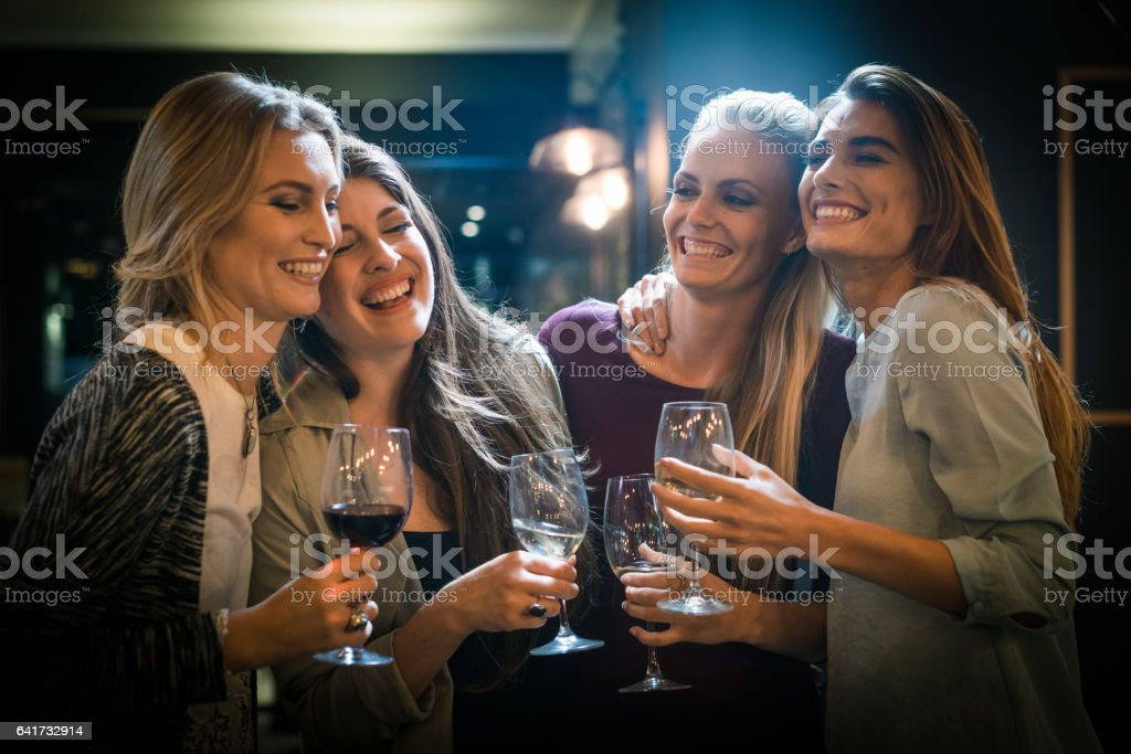Cheerful female friends enjoying drinks in bar stock photo