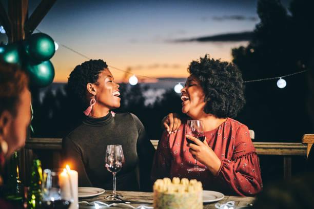 Cheerful female friends enjoying wine at birthday stock photo