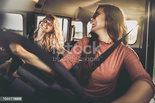 Young happy women communicating while having fun on their road trip.