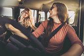 Cheerful female friends talking during a road trip in a car.