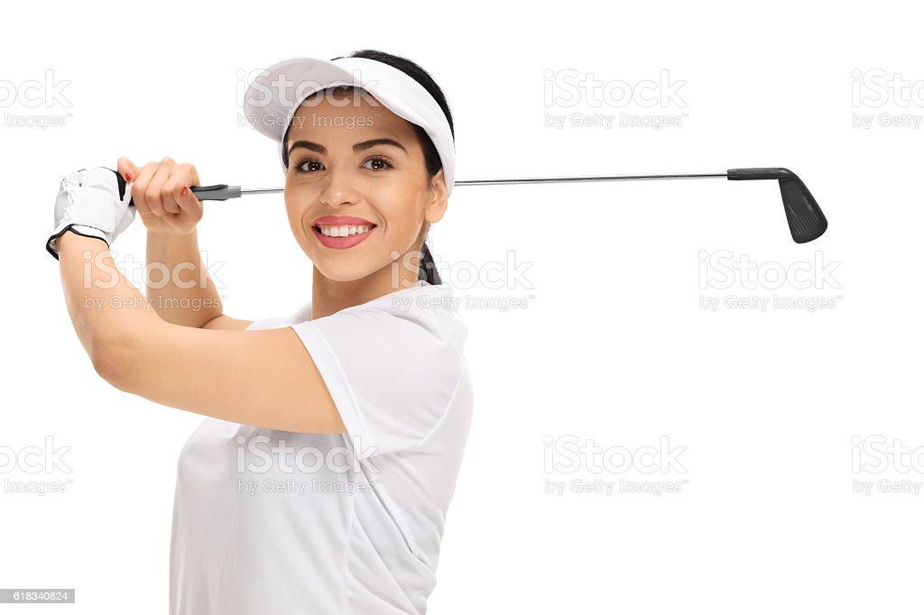 Cheerful female golf player swinging a golf bat stock photo