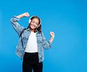 Happy cute teenage girl wearing oversized denim jacket, white t-shirt, black jeans, backpack and headphones standing against blue background. Pretty girl listening to the music and dancing. Portrait of smiling teenager.