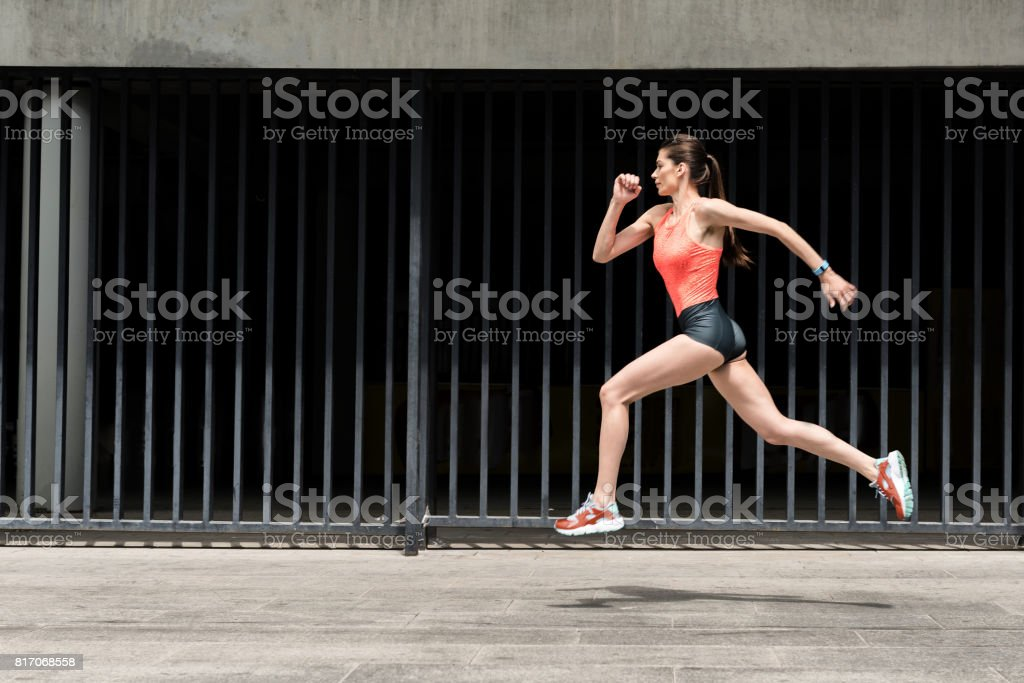 Cheerful female jogger training outdoors stock photo