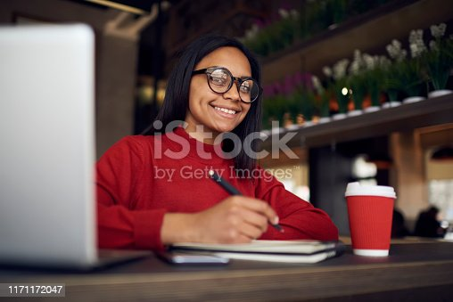 istock Cheerful female journalist working remotely in coworking space while sitting at desktop with textbook and laptop and planning schedule for next week,smiling woman feeling good from time for autodidact 1171172047