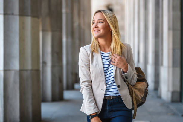 Cheerful Female Law Student Walking in University Colonnade stock photo