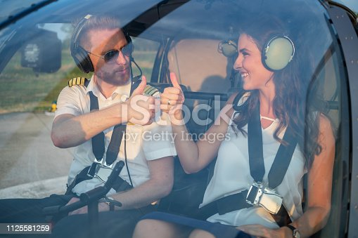 Cheerful female passenger and helicopter pilot sitting in cockpit and giving thumbs up ready for take off