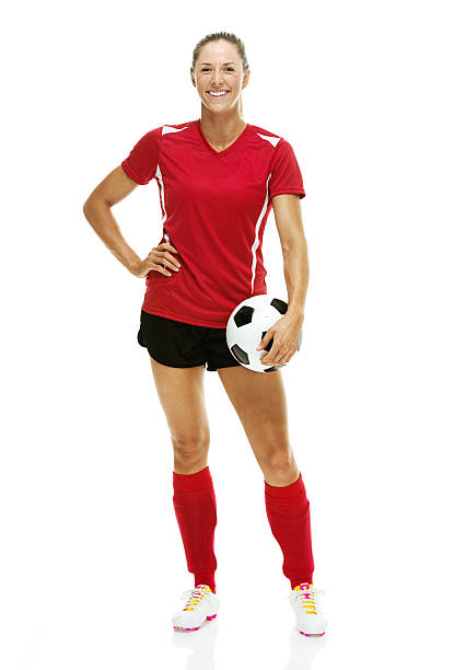 Cheerful female soccer player holding ball Cheerful female soccer player holding ballhttp://www.twodozendesign.info/i/1.png akimbo stock pictures, royalty-free photos & images