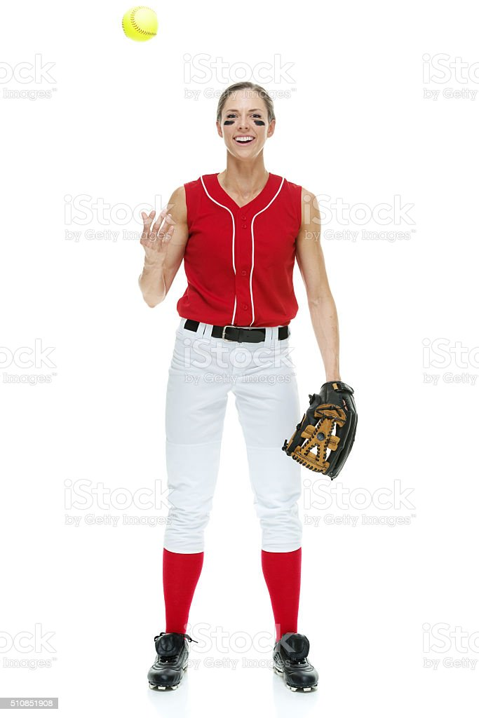 Cheerful female softball player playful with ball stock photo