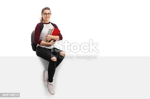 istock Cheerful female student with backpack and books sitting on panel 649749212