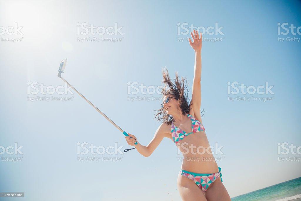 Cheerful Female Taking Selfie At The Seashore stock photo
