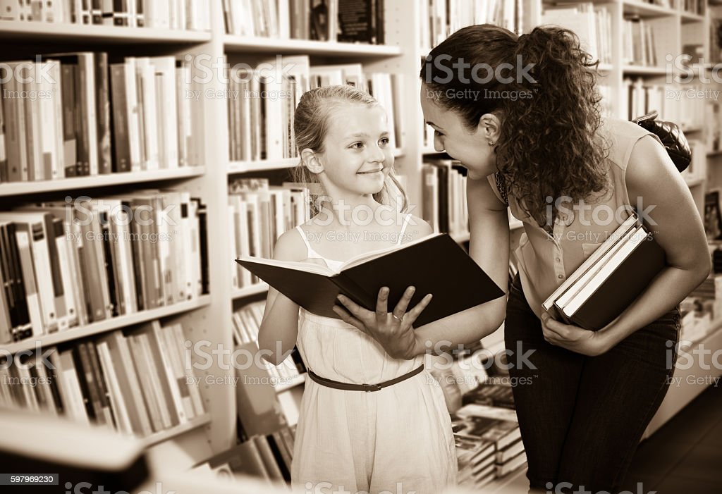 Cheerful female with small girl  in bookstore stock photo