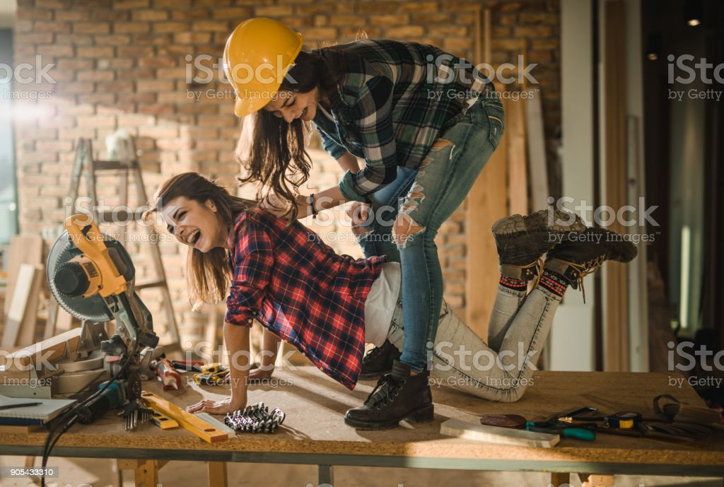 Cheerful female workers having fun on the table at construction site. stock photo