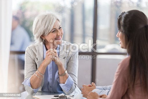 istock Cheerful financial advisor meets with clients 1055689256