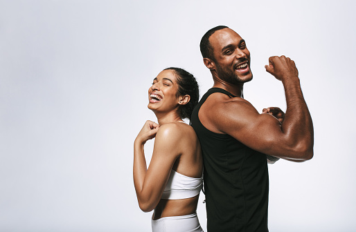 Smiling fitness couple standing back to back against white background. Fit couple showing arm muscles standing together.
