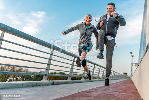 Health fit mature couple running together during a magnificent day - Athletic friends doing sport outdoor - Sporty gray hair people training with jump exercises - Relationship, sport, lifestyle concept. Photo of Fitness couple jumping happy at the bridge in the city with a clear blue sky.
