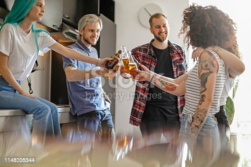Cheerful flatmates giving a toast with bottled beer, standing in the kitchen