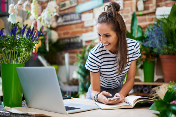 Cheerful florist leaning on counter in her shop looking at laptop with client orders stock photo