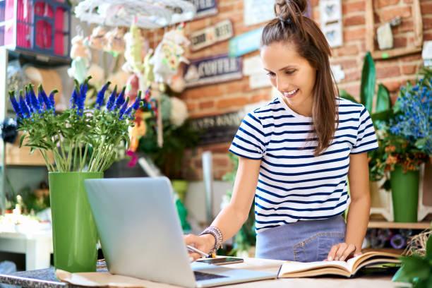 fleuriste bonne humeur regardant portable et écrire des commandes client dans carnet - fleuriste photos et images de collection