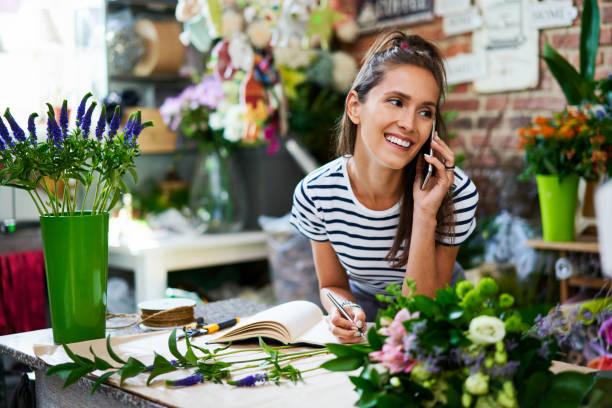 Cheerful florist on phone with client and writing down their order stock photo