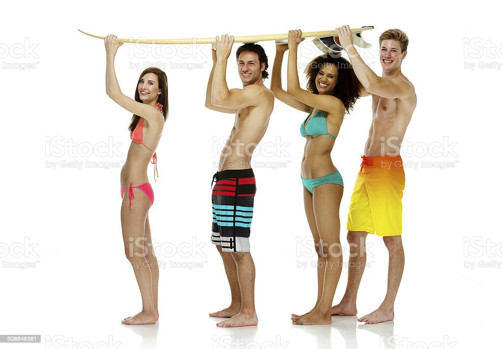 Cheerful four friends holding surfboard stock photo