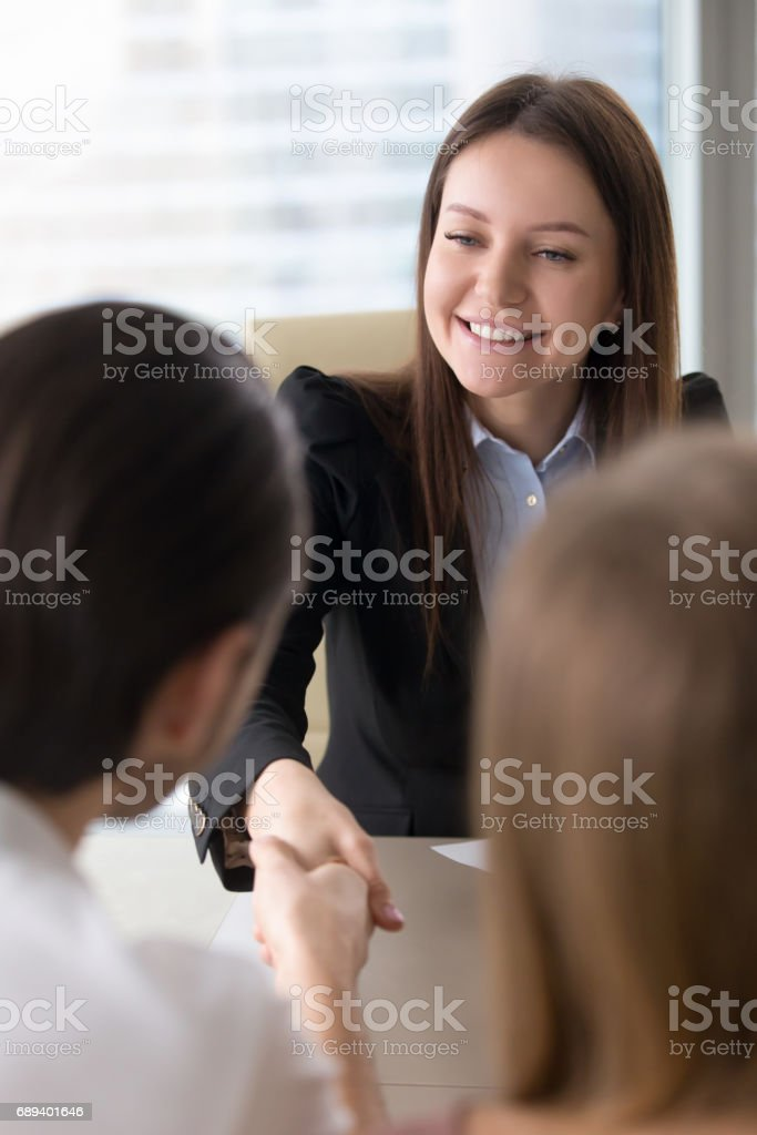 Cheerful friendly businesswoman working with young couple, shaking hands, vertical stock photo