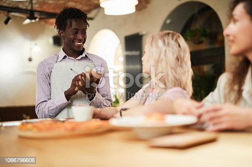 Friendly waiter talking to guests