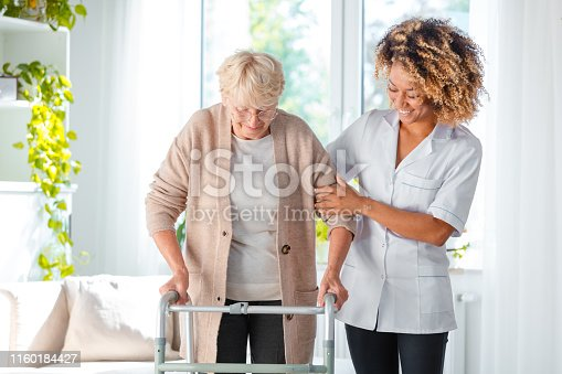 Cheerful friendly nurse helping senior woman to use walking frame