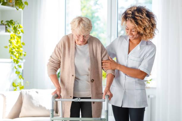 vrolijke vriendelijke verpleegkundige helpen oudere vrouw - thuiszorg stockfoto's en -beelden