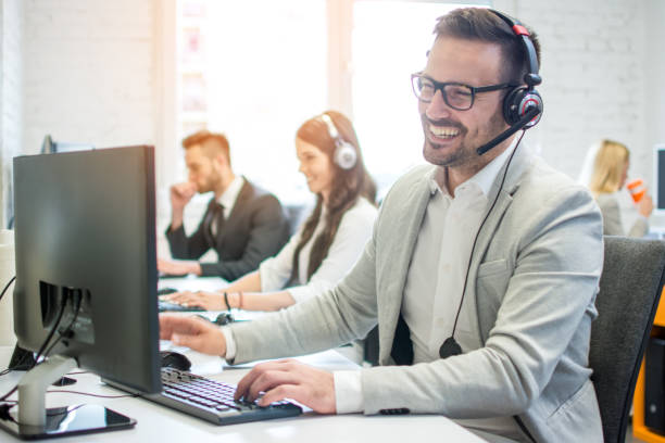 Cheerful friendly online technical operator agent with headphones and microphone talking with client in customer support office stock photo