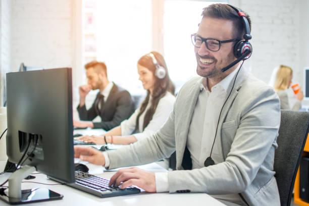 Fröhlich freundliche Online-Techniker Agent mit Kopfhörer und Mikrofon im Gespräch mit dem Kunden im Kundendienst – Foto