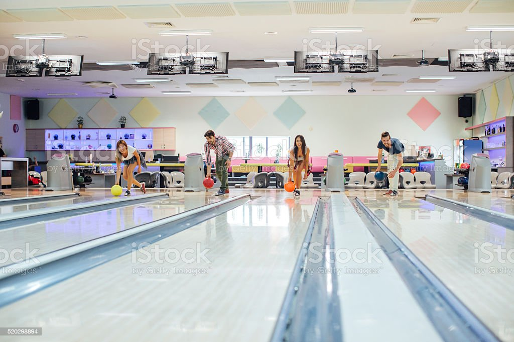 Cheerful Friends Bowling Together. stock photo