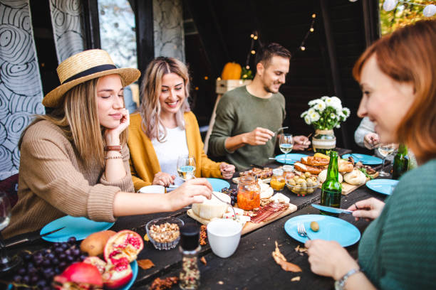 Cheerful friends celebrating their reunion with amazing Italian cheese board and wine stock photo
