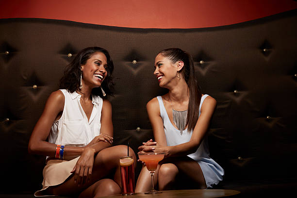 cheerful friends conversing on sofa in nightclub - club sofa stock-fotos und bilder