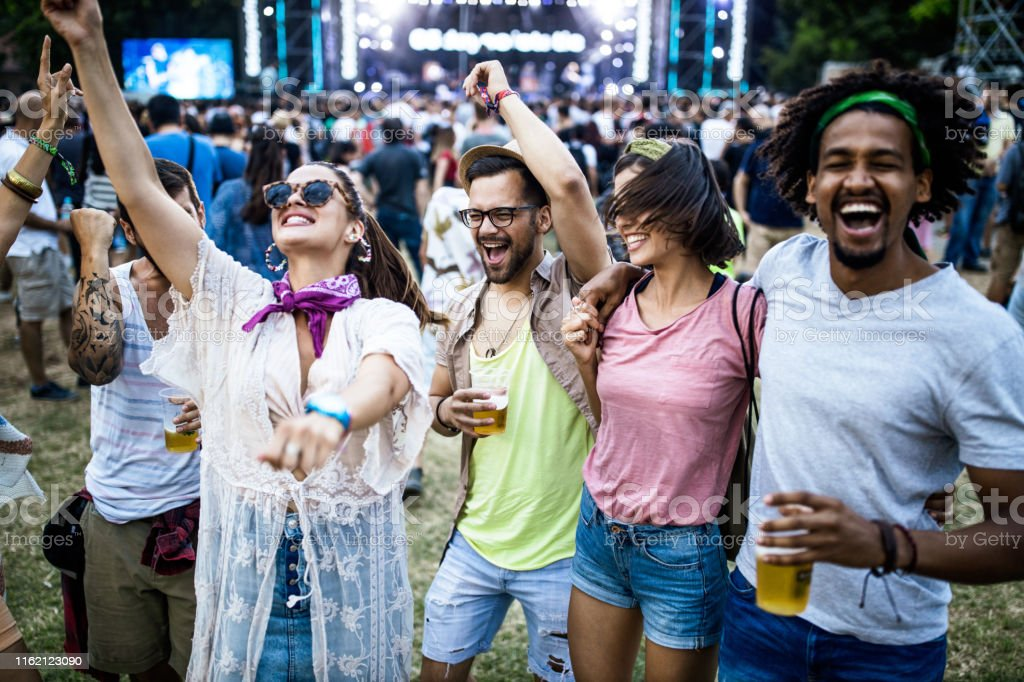 Group of young cheerful friends having fun while dancing on a music...