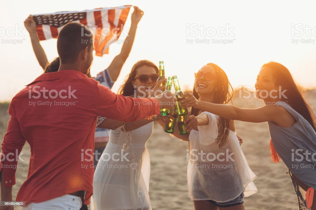 Cheerful friends drinking beer on beach and cheering royalty-free stock photo