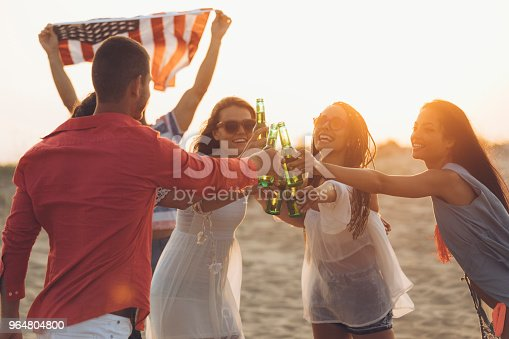 Cheerful Friends Drinking Beer On Beach And Cheering Stock Photo & More Pictures of 30-34 Years