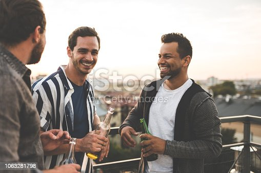 Group of male friends standing together at rooftop with drinks and chatting. Cheerful friends enjoying at terrace party.