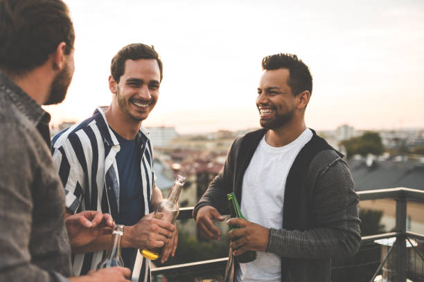 Cheerful friends enjoying at rooftop party stock photo