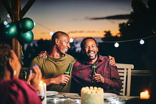 Cheerful male friends enjoying beer together. Men and woman are sitting at table. They are having fun in birthday party at night.