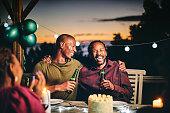 istock Cheerful friends enjoying beer in birthday party 1220700088
