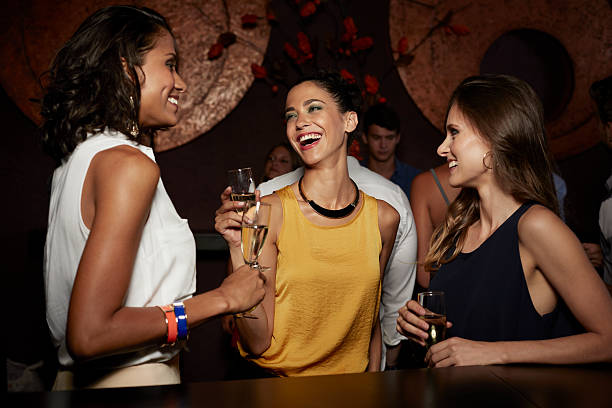 Cheerful friends enjoying champagne in nightclub stock photo