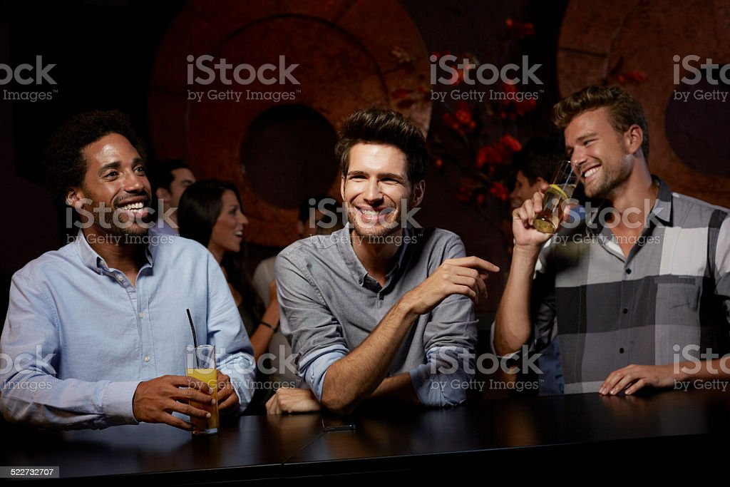 Cheerful friends enjoying drinks in nightclub stock photo