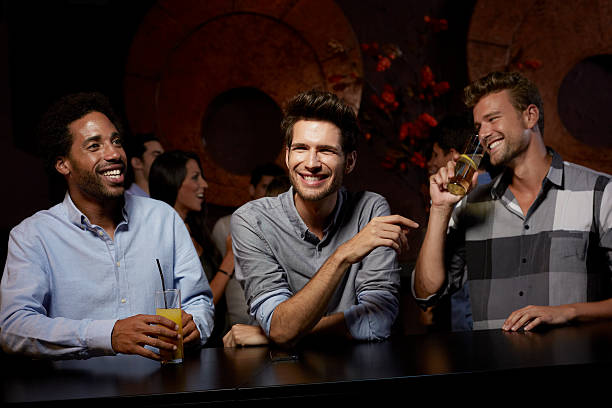 cheerful friends enjoying drinks in nightclub - incidental people stock pictures, royalty-free photos & images