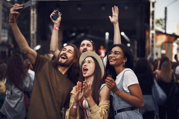 cheerful friends making selfie at outdoor music festival - concert selfie stock photos and pictures